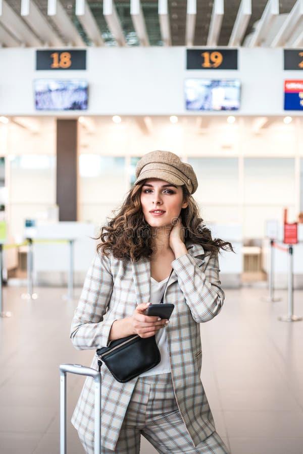 Ung h?rlig kvinna som l?ser telefonmeddelanden i v?ntande rum f?r flygplats royaltyfria bilder