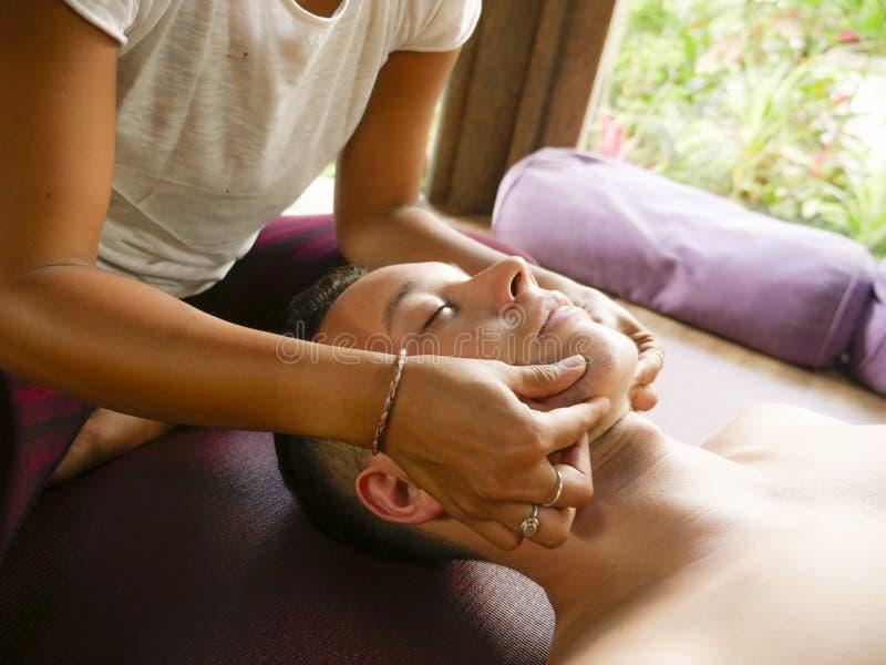 Ung h?rlig och exotisk asiatisk thail?ndsk terapeutkvinna som ger det traditionella huvudet och ansikts- Balinesemassage till den royaltyfri bild