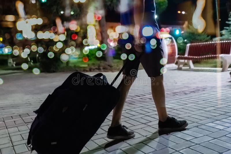 ung handelsresande som går till resasemestern med rullat bagage på natt s royaltyfri fotografi