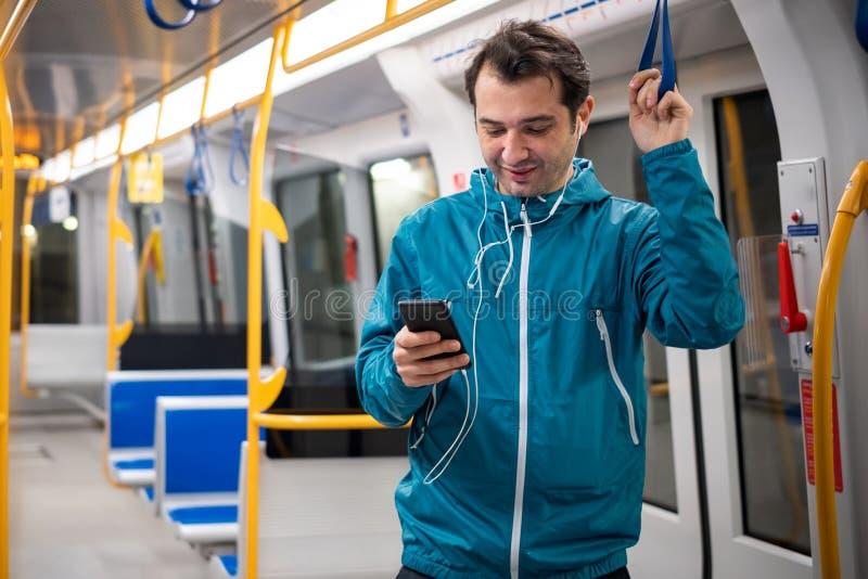 Ung handelsresande som l?ser det sociala n?tverket p? mobiltelefonen p? g?ngtunneltunnelbanakollektivtrafik royaltyfri bild