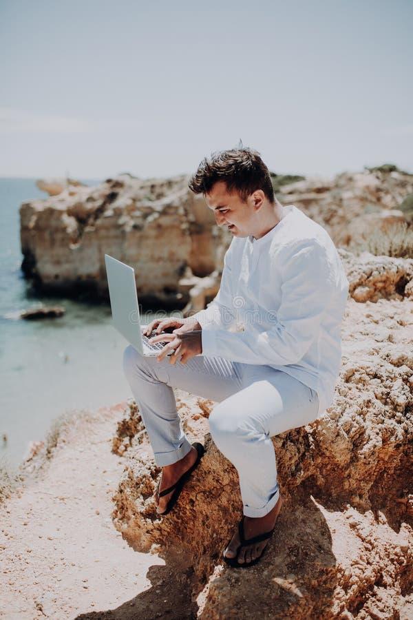 Ung handelsresandeblogerman som sitter rymma bärbara datorn på den soliga naturliga stranden för hav royaltyfria bilder