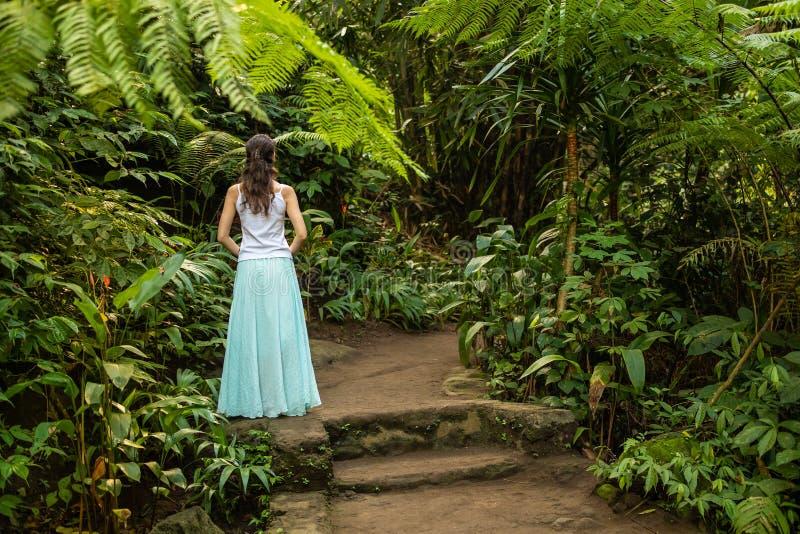 Ung handelsresandekvinna som går i den tropiska skogen, Ubud, Bali Sikt fr?n baksida royaltyfri bild