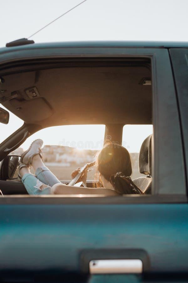 Ung handelsresandekvinna som spelar gitarren inom bilen för jeep som 4x4 gör en reslustsemester på solnedgången i sommar fotografering för bildbyråer