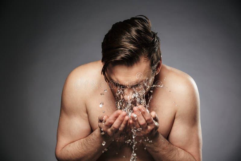 Ung hansdomeman för stående som tvättar hans framsida royaltyfria foton