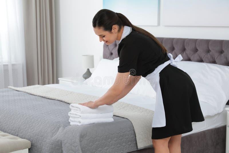 Ung hembiträde som sätter bunten av nya handdukar på säng arkivbild