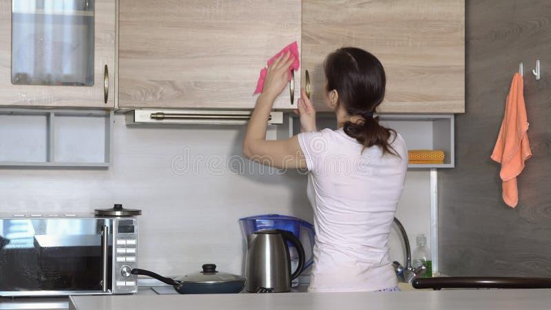 Ung hemmafru som gör ren lägenheten i köket arkivfoto