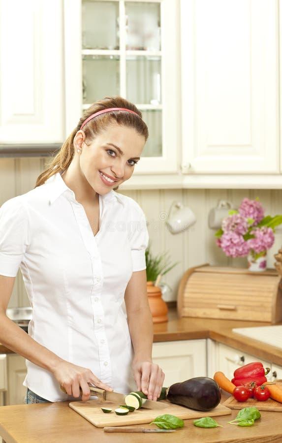 Ung hemmafru som klipper den nya grönsaken royaltyfria bilder