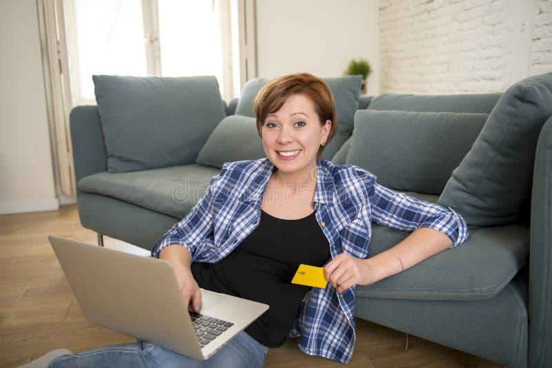 Ung hemmastadd soffasoffa för attraktiv och lycklig kvinna med kreditkort- och datorbärbar datorshopping på linje- eller bankröre royaltyfri foto