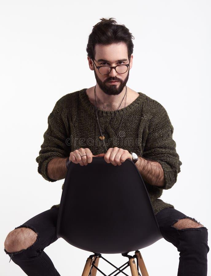 Ung hipster på stol i studio royaltyfria bilder