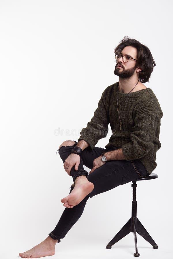 Ung hipster som poserar på stol arkivfoton