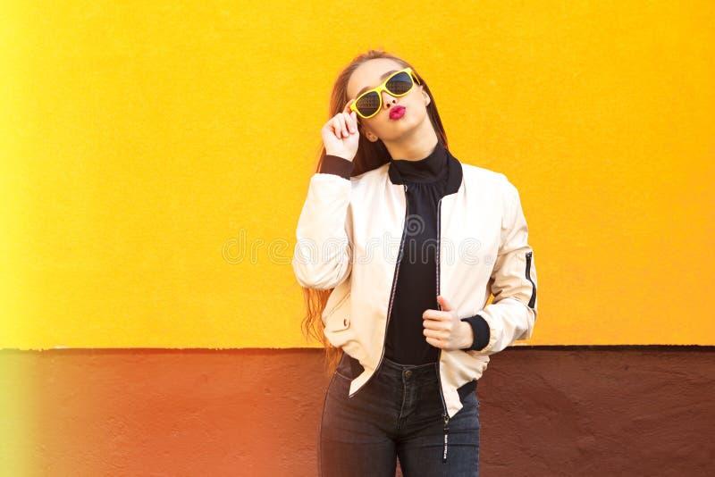 Ung hipsterflicka i gul solglasögon som kysser på den orange väggen stads- stil Tappning Ilsken blick och ljus royaltyfri fotografi