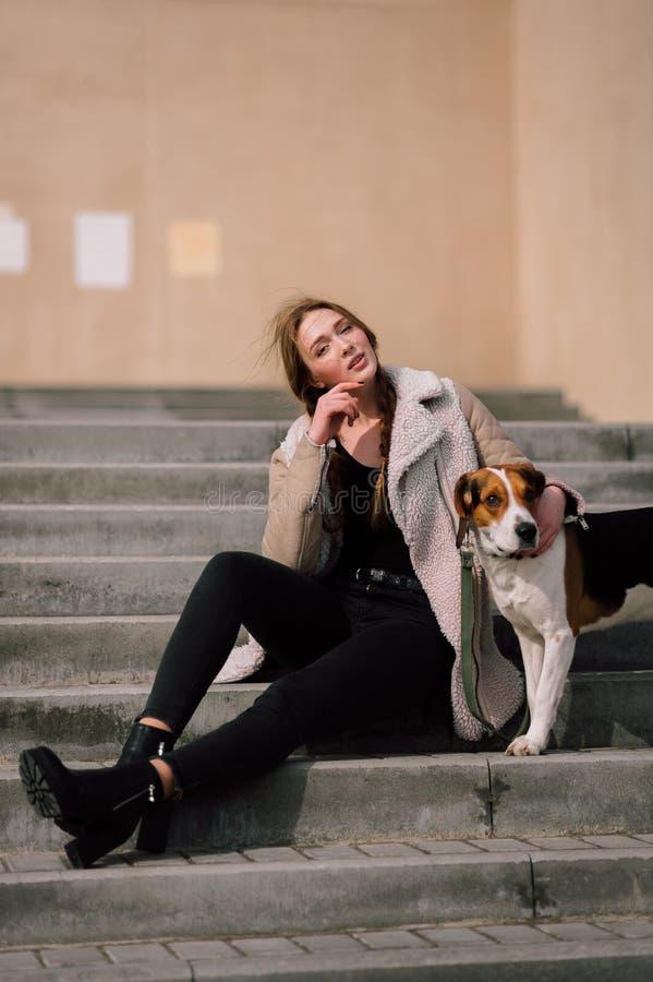Ung hipsterflicka med hennes älsklings- estonian hundhund som spelar och har roligt utomhus- i parkera royaltyfri foto