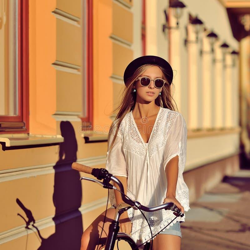 Ung hipsterflicka på en retro cykel utomhus- stående för mode arkivbild
