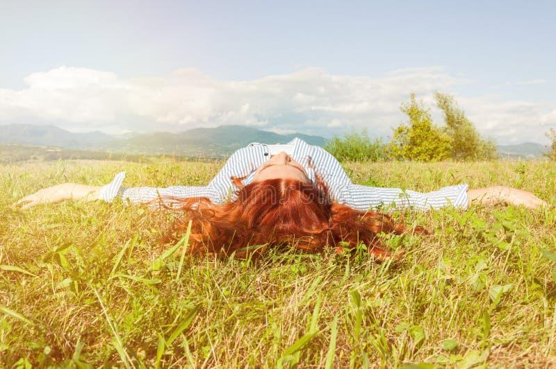 Ung hipsterflicka som kopplar av på gräset royaltyfria foton
