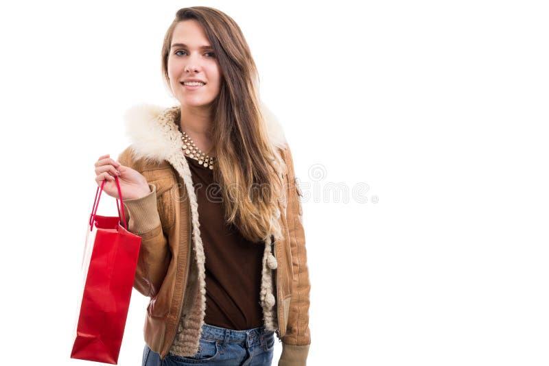 Ung hipsterflicka som rymmer den röda shoppingpåsen arkivbild