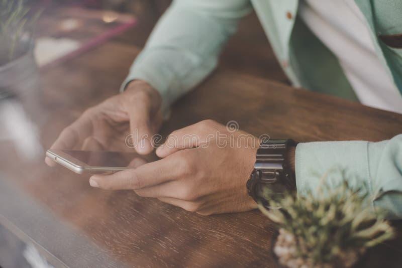 Ung hipstergrabb som smsar med hans mobiltelefon på stången royaltyfri foto