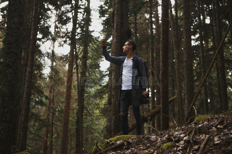 Ung hipstergrabb som tar fotoet på hans mobiltelefonkamera av ett härligt landskap, medan stå den near sjön, skäggig man royaltyfri foto