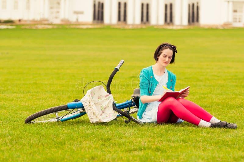 Ung hipsterkvinnlig med cykelhandstil något på anteckningsboken fotografering för bildbyråer
