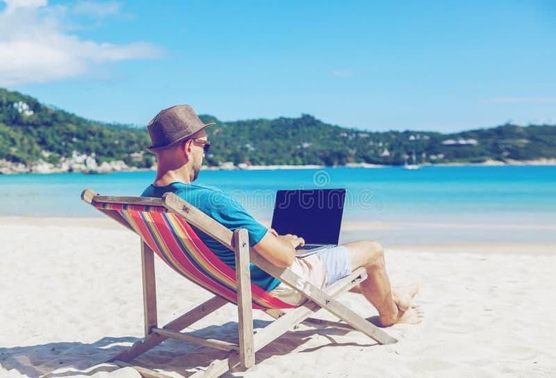 Ung hipsterman med bärbara datorn på den tropiska stranden Lopp vacatio arkivfoto