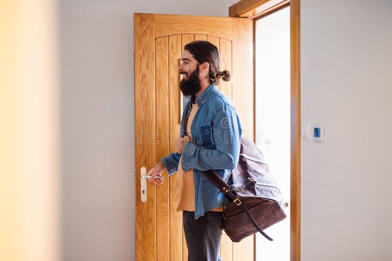 Ung hipsterman med den skrivande in ytterdörren för påse när kommande tillbaka hem fotografering för bildbyråer