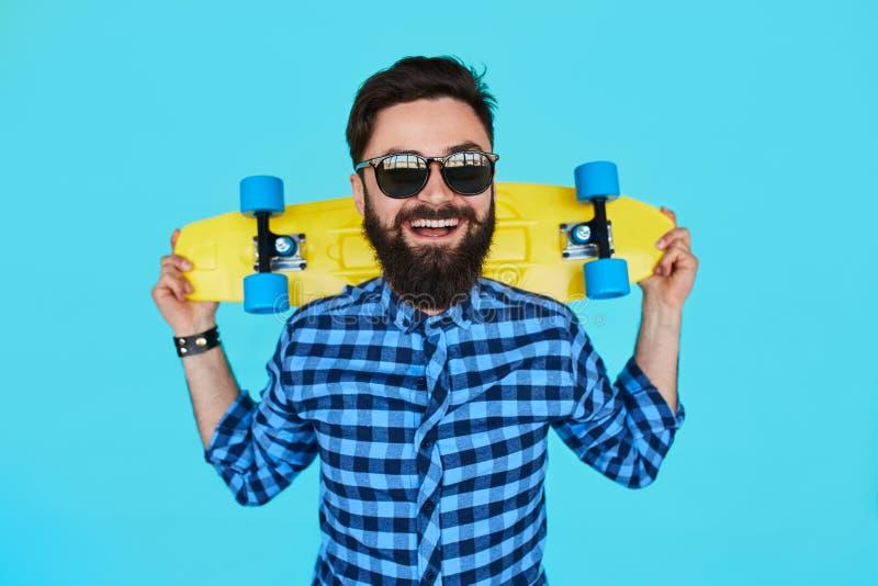 Ung hipsterman med en skateboard royaltyfria bilder
