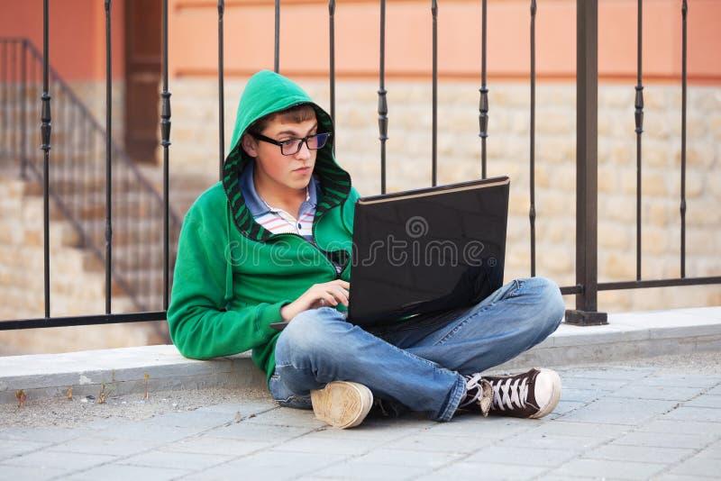 Ung hipsterman som använder bärbara datorn i stadsgata royaltyfri bild