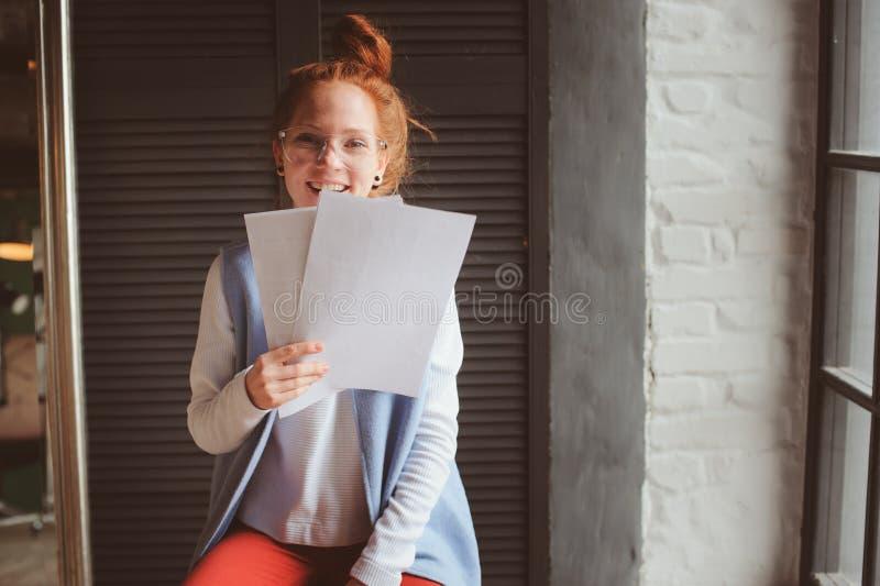 Ung hipsterstudentkvinna eller idérikt frilans- märkes- arbete på projekt Hållande coursework- eller affärsplan arkivbild