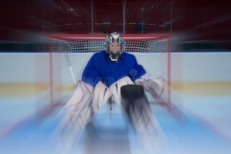 Ung hockeygoalie- och flygpuck arkivbilder