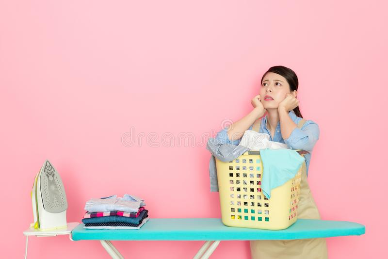 Ung houseworkerkvinna som förbereder strykningkläder royaltyfri fotografi