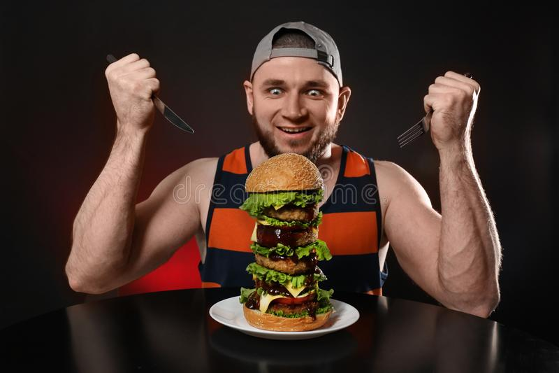 Ung hungrig man med bestick som äter den enorma hamburgaren royaltyfri bild