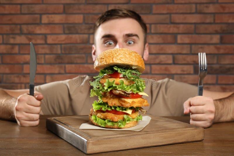 Ung hungrig man med bestick som äter den enorma hamburgaren fotografering för bildbyråer