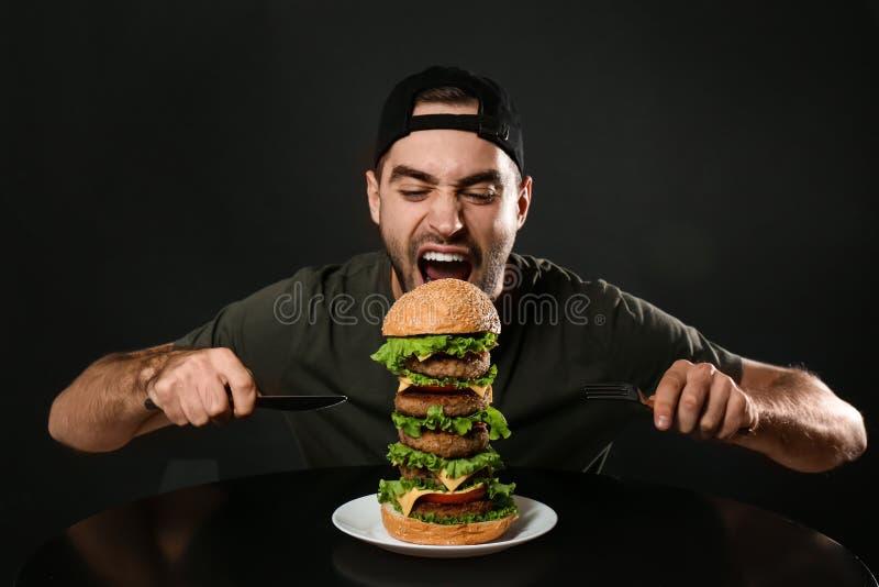 Ung hungrig man med bestick som äter den enorma hamburgaren royaltyfri foto