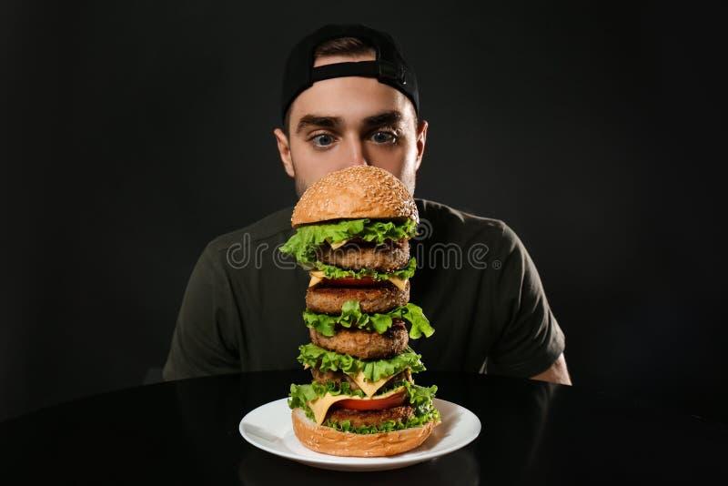 Ung hungrig man och enorm hamburgare royaltyfri fotografi