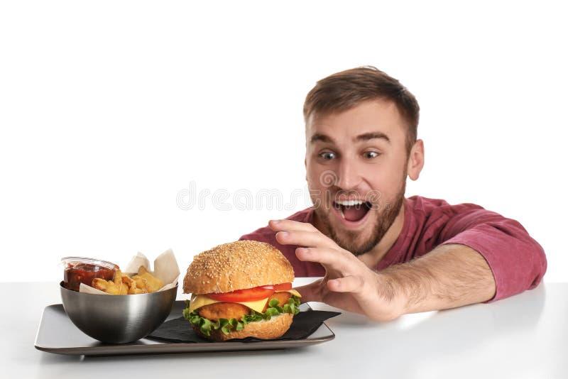 Ung hungrig man och platta med pommes frites och den smakliga hamburgaren royaltyfri foto