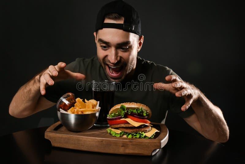 Ung hungrig man och smaklig hamburgare som tjänas som på träbräde med pommes frites fotografering för bildbyråer