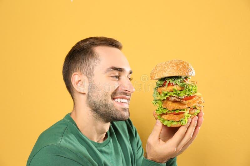 Ung hungrig man som äter den enorma hamburgaren royaltyfri bild