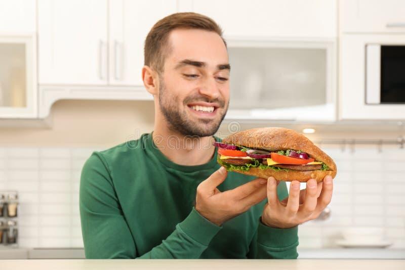 Ung hungrig man som äter den smakliga smörgåsen royaltyfri fotografi