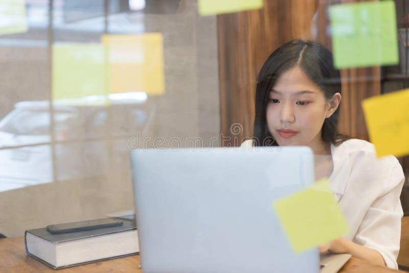 Ung idérik asiatisk kvinna som arbetar i modernt kontor royaltyfria bilder