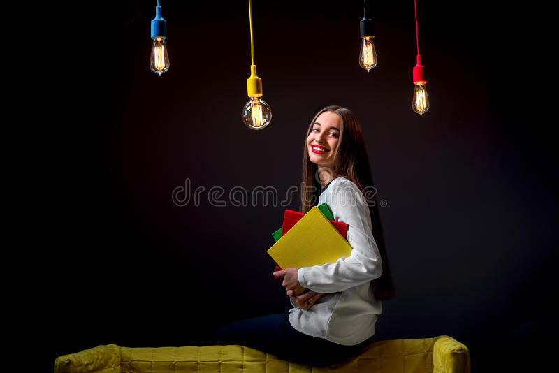 Ung idérik student med färgrika lampor och böcker royaltyfri fotografi