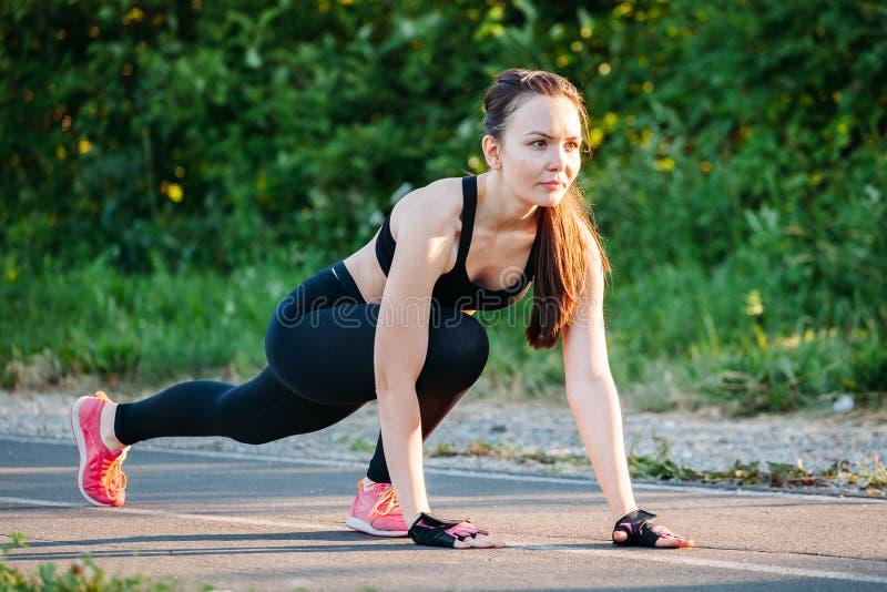 Ung idrotts- kvinna som förbereder sig att köra på för att parkera, utomhus begrepp av en sund livsstil arkivbild
