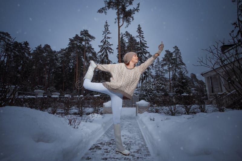 Ung idrotts- kvinna som g?r yoga i tr?na i vinter arkivfoto