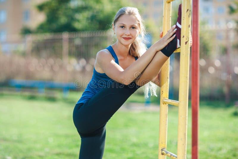 Ung idrotts- kvinna som utomhus sträcker benet på stången fotografering för bildbyråer