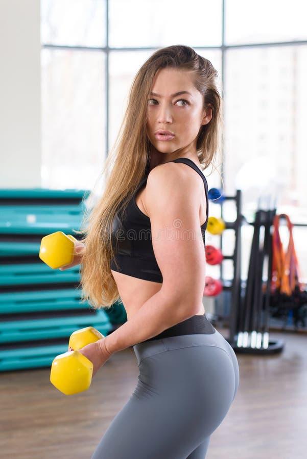 Ung idrotts- kvinnautbildning med hantlar på idrottshallen Kondition och sunt livsstilbegrepp härlig caucasian flicka royaltyfri bild