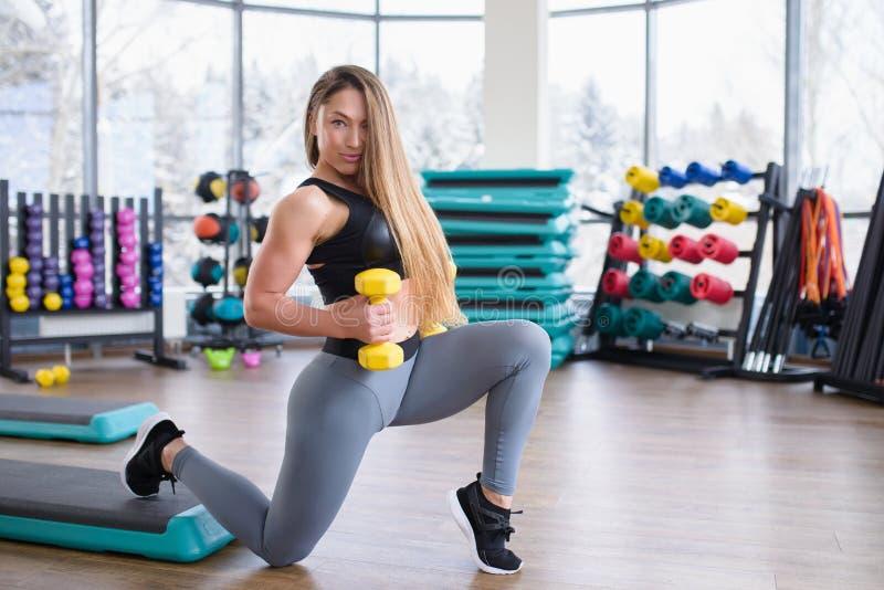 Ung idrotts- kvinnautbildning med hantlar på idrottshallen Kondition och sunt livsstilbegrepp härlig caucasian flicka fotografering för bildbyråer