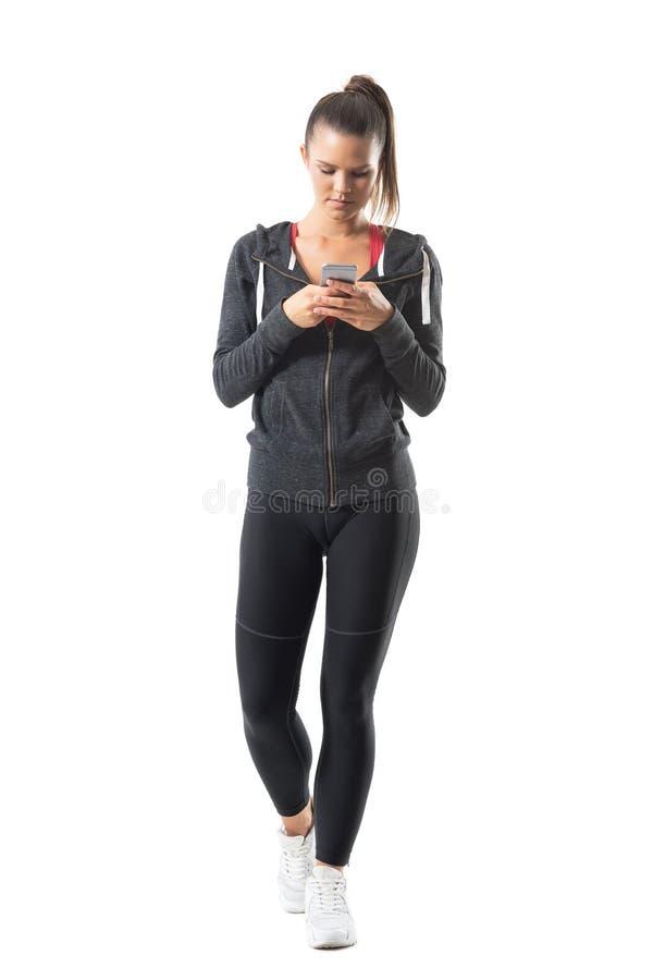 Ung idrotts- kvinnlig löpare i sportswear genom att använda mobiltelefonen fotografering för bildbyråer