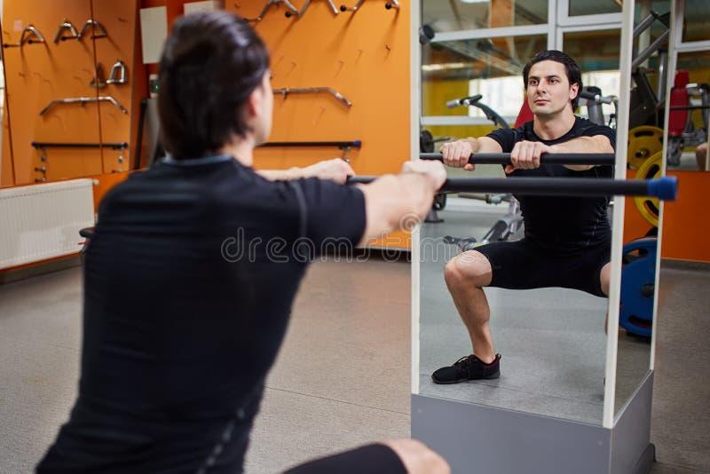 Ung idrotts- man i svart sportwear med stången av skivstången som framme böjer muskler i idrottshall av spegeln arkivbild