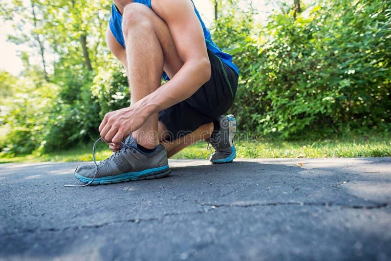 Ung idrotts- man som binder hans skosnöre fotografering för bildbyråer