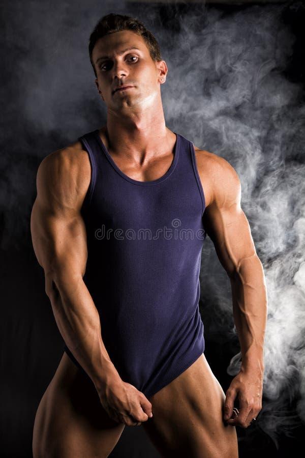 Ung idrotts- man som drar ner tanktop på den rev sönder muskulösa torson arkivfoton