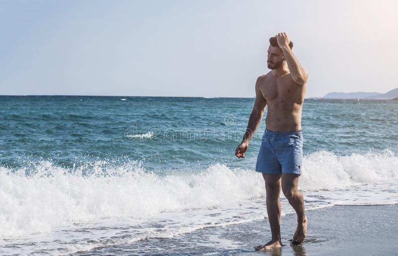 Ung idrotts- man som går på stranden royaltyfria foton