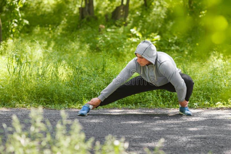 Ung idrotts- man som gör sträcka övningar som är utomhus- Den sunda mannen som in utarbetar, parkerar royaltyfria foton
